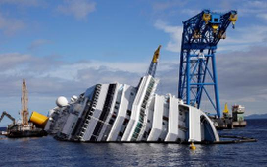 A general view of the capsized cruise liner Costa Concordia surrounded by cranes, near the harbour of Giglio Porto