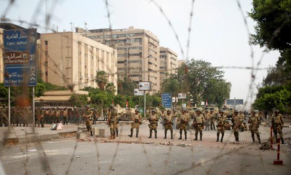 Members of the Republican Guards stand in line at a barricade blocking protesters supporting deposed Egyptian President Mohamed Mursi near a Republican Guards headquarters in Cairo