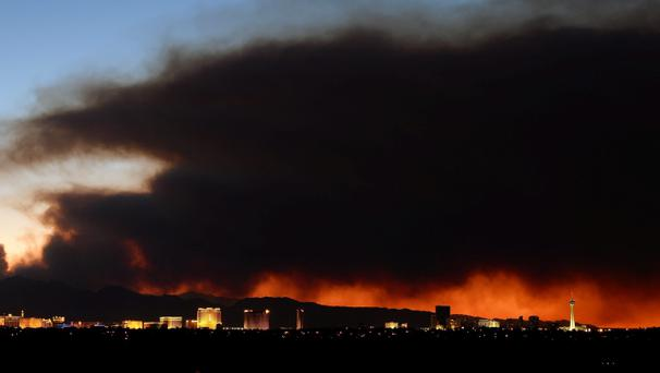 Smoke from the Carpenter 1 fire in the Spring Mountains range is illuminated by the setting sun as it billows behind hotel-casinos on the Las Vegas Strip