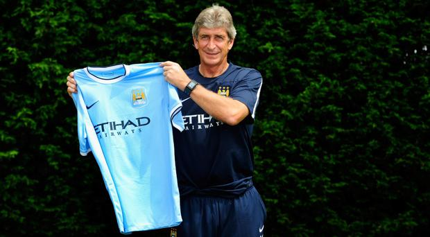Manchester City manager Manuel Pellegrini poses with a team shirt after his first media conference at Carrington Training Ground
