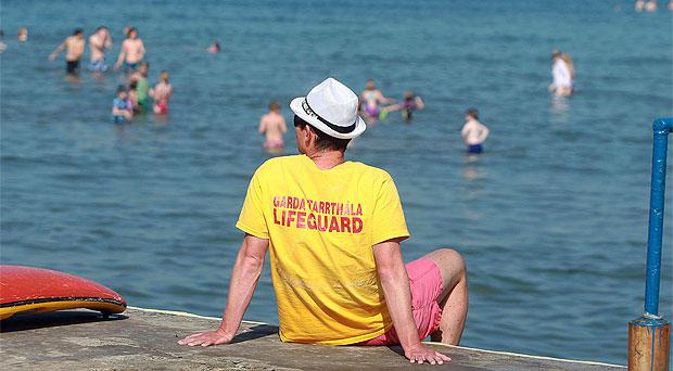 A life guard watches over members of the public who are enjoying the good weather at Seapoint, Dublin