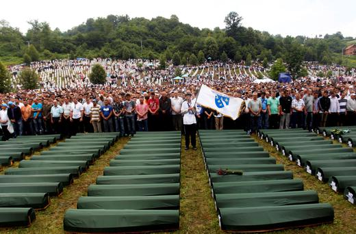 Bosnians pray in front of 409 coffins of newly identified victims of the 1995 Srebrenica massacre in the Potocari Memorial Center.