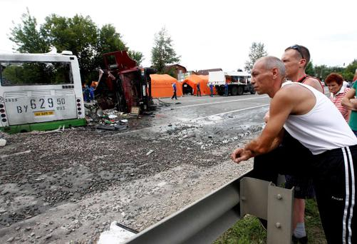 Bystanders watch as members of the emergency services work at the scene of a collision between a bus and a truck outside Moscow July 13, 2013