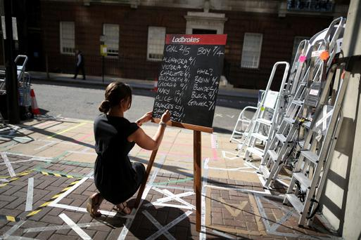 Ladbrokes executive writes odds for the royal baby on a chalk board in front of the Lindo Wing at St Mary's Hospital.