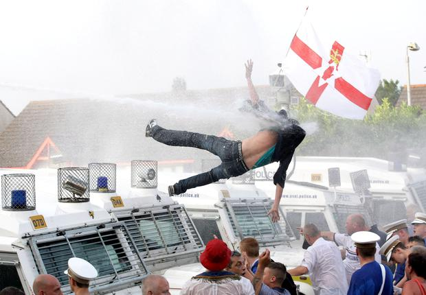 A man on top of a police landrover gets blown off by the water cannon at Woodvale yesterday. Picture by David Fitzgerald, Belfast Telegraph