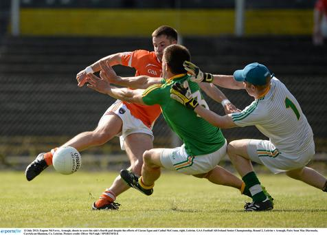 Eugene McVerry, Armagh, shoots to score his side's fourth goal despite the efforts of Ciaran Egan and Cathal McCrann