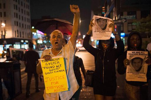 Protesters gesture as they rally in response to the acquittal of George Zimmerman in the Trayvon Martin trial, in the Harlem neighborhood of New York July 14, 2013