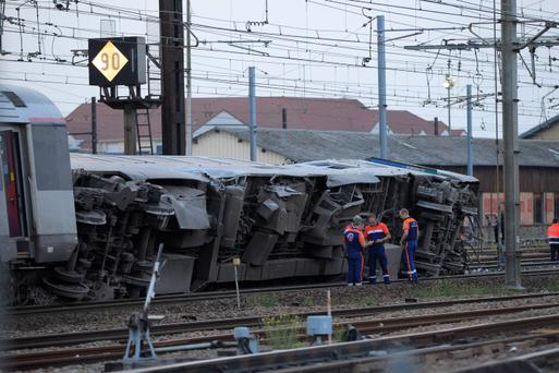 Rescue workers stand next to the wreckage of a derailed intercity train at the Bretigny-sur-Orge station near Paris July 12, 2013