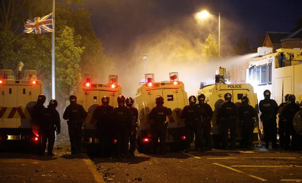 Riot police deploy a water cannon after being attacked by loyalist protesters in north Belfast