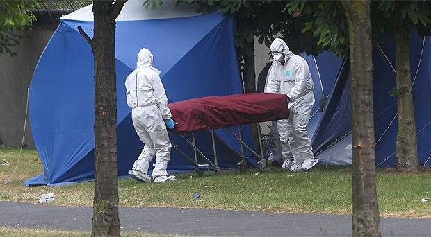 Garda forensics officers remove the victim's body from the scene