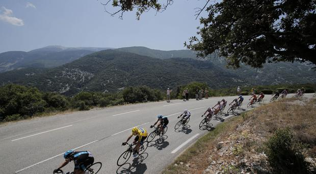 The pack with Christopher Froome of Britain, wearing the overall leader's yellow jersey, passes during the sixteenth stage of the Tour de France cycling race over 168 kilometers (105 miles) with start in in Vaison-la-Romaine and finish in Gap, France, Tuesday July 16, 2013.