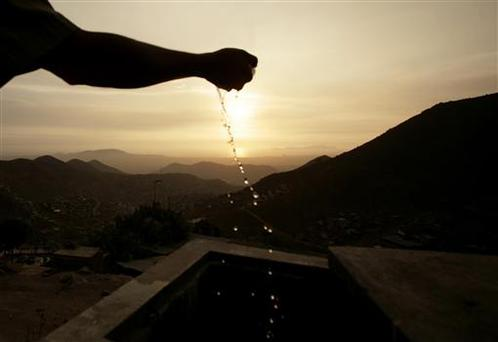 Noel Neyra, a resident, cups a handful of water collected from fog catching nets that provide water to the barren hillside community of Bellavista del Paraiso, near Peru's capital Lima, REUTERS/Mariana Bazo