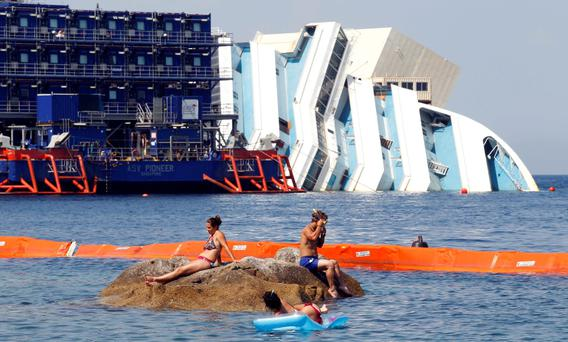 People sunbathe in front of the capsized cruise liner Costa Concordia lying surrounded by cranes outside Giglio harbour July 17, 2013