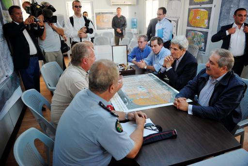 US Secretary of State John Kerry (2nd R) and Jordanian Foreign Minister Nasser Judeh (R) listen to a briefing by Zaatari refugee camp manager Kilian Kleinschmidt (L, across from Kerry) at the refugee camp near the Jordanian city of Mafraq.