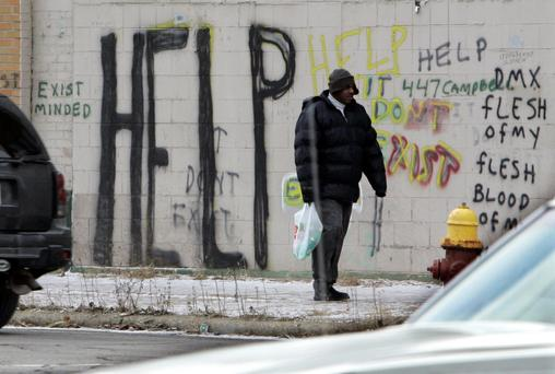 A pedestrian walks by graffiti in downtown Detroit.