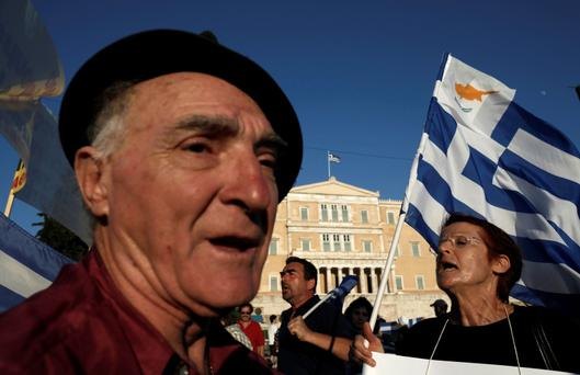 Protesters shout slogans in front of the parliament during a rally against the visit of the German Finance Minister Wolfgang Schaeuble in Athens.