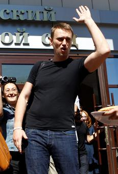 Russian opposition leader Alexei Navalny greets supporters and journalists outside a court building in Kirov, July 19, 2013. A Russian court temporarily released Navalny from custody on Friday, but placed him under travel restrictions, while he awaits the outcome of an appeal against his sentence to five years in jail. REUTERS/Sergei Karpukhin (RUSSIA - Tags: CRIME LAW POLITICS CIVIL UNREST)