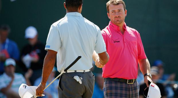 Graeme McDowell of Northern Ireland shakes hands with Tiger Woods of the United States after finishing their second round