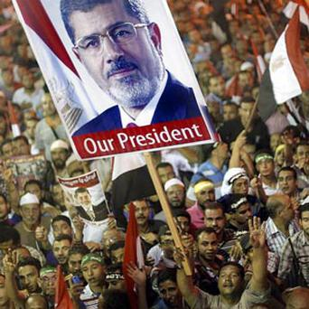 Supporters of Egypt's ousted President Mohammed Morsi hold his poster and wave national flags as they protest at a park in front of Cairo University