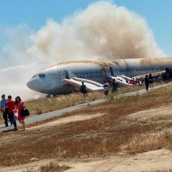Passengers evacuate from Asiana Airlines Boeing 777 aircraft after a crash landing