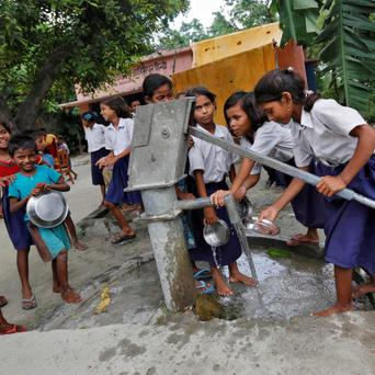 Schoolchildren wash their plates before having their free mid-day meal, distributed by a government-run primary school, at Brahimpur village in Chapra district of the eastern Indian state of Bihar