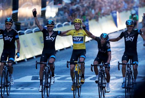 Christopher Froome of Britain, winner of the centenary Tour de France cycling race, celebrates his overall victory with team mates as they cross the finish line