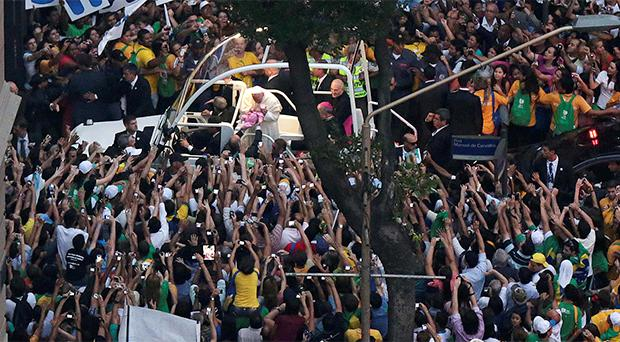 Pope Francis kisses a baby while greeting the crowd of faithful from his popemobile in downtown Rio de Janeiro