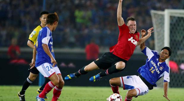 Manchester United's Phil Jones flies through the air after a challenge by Andrew Kumagai of Yokohama