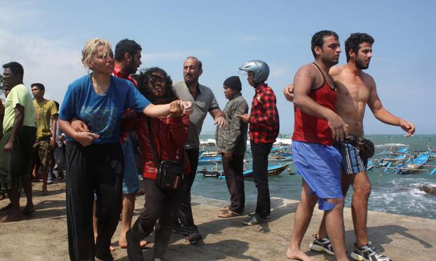Suspected asylum seekers, who were on a boat that capsized late on Tuesday after hitting a reef off the coast of Sukapura, arrive at Jayanti beach.