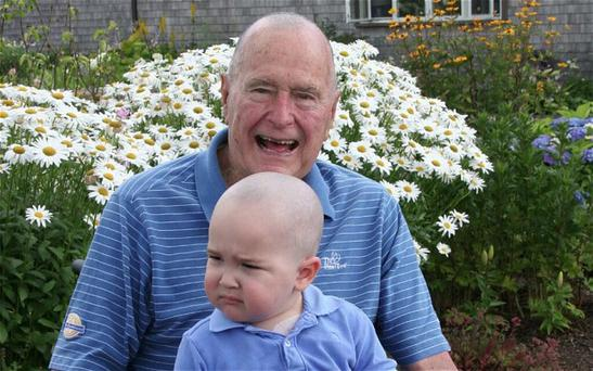 George Bush shaved his head to raise funds for the son of one of his body guards who is suffering from leukemia