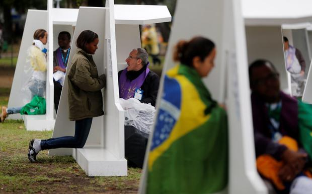 People confess at the confessional booths set up at Quinta da Boa Vista park at the World Youth Day in Rio