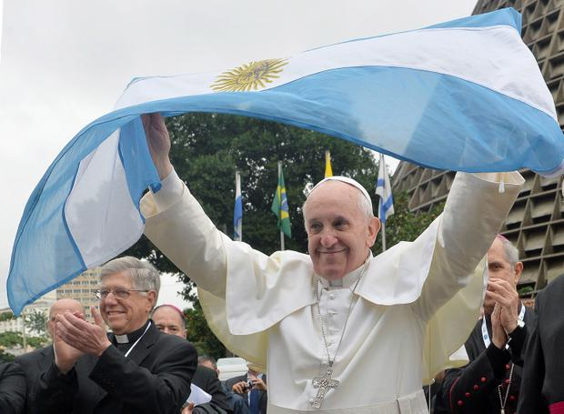 Pope Francis meets with Argentinian pilgrims as he waves their national flag in Rio de Janeiro