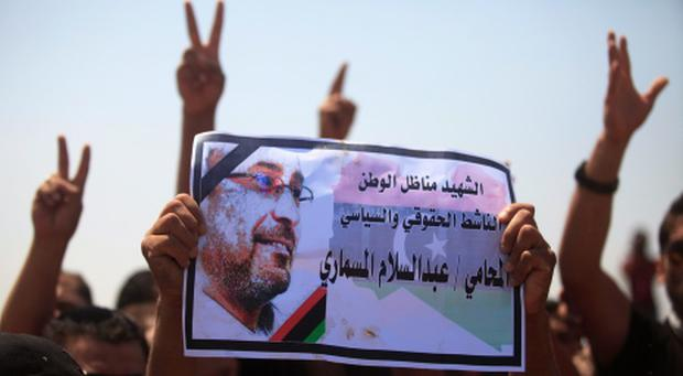 Men hold up a picture of slain lawyer and prominent Libyan political activist Abdelsalam al-Mosmary, during his funeral in Benghazi July 27, 2013. REUTERS/Esam Al-Fetori