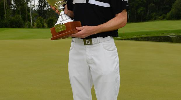 Michael Hoey of Northern Ireland celebrates with the trophy after winning the Final round of the M2M Russian Open
