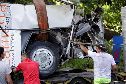 A crane lifts up the wreckage of a bus following a crash near Avellino, southern Italy, Monday, July 29, 2013