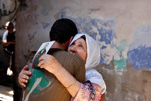 The mother of Palestinian Ateya Abu Moussa, who has been held prisoner by Israel for 20 years, reacts as she is hugged by her grandson after hearing news on the possible release of her son, in Khan Younis in the southern Gaza Strip July 28, 2013. Abu Moussa was expected to be among more than 100 Arab prisoners to be released as a step to renew stalled peace talks with the Palestinians ahead of plans to convene negotiators in Washington later this week