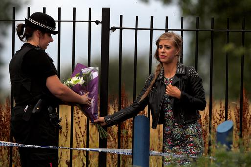 A well-wisher hands over some flowers to a police officer at the scene of a stabbing in Moston, Manchester