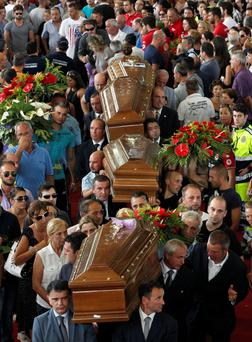 People pay tribute to the coffins of victims of a coach crash at the end of the funeral service at the Monteruscello Palasport near Pozzuoli July 30, 2013
