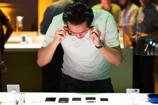 A man uses Google Glass to photograph examples of Motorola's new Moto X phone next to other mobile phones at a launch event in New York
