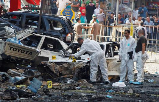 Forensic inspectors examine the site of a car bomb