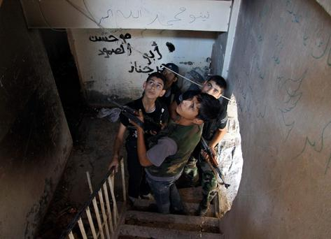 Free Syrian Army fighters look up while standing on a flight of stairs, as they take cover inside a building in Deir al-Zor