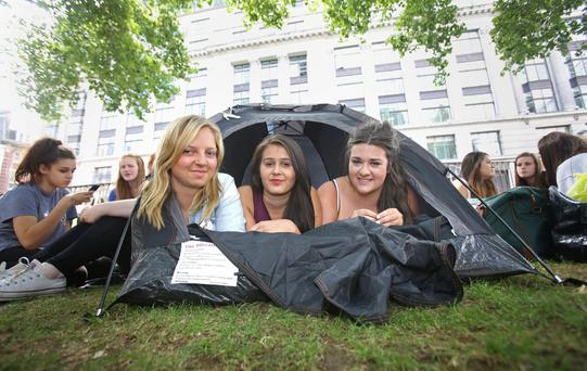One Direction fans Amelia Troughton-Smith, 17, Ashah Xhafa, 17, and Jessica Facey, 17, who arrived this morning at Leicester Square in London the band's arrivals of the premiere tomorrow of their film, This Is Us. PRESS ASSOCIATION Photo.