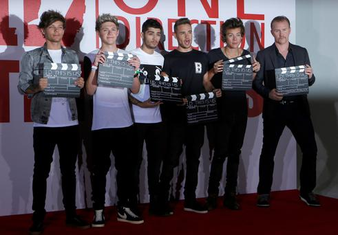 One Direction's Louis Tomlinson, Niall Horan, Zayne Malik, Liam Payne, Harry Styles, and Director Morgan Spurlock, pose for photographers during a photocall for their film 'One Direction; This is Us' in London