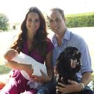 Britain's Prince William and his wife Catherine pose in the garden of the Middleton family home in Bucklebury, southern England, with their son Prince George, cocker spaniel Lupo (R) and Middleton family pet Tilly.