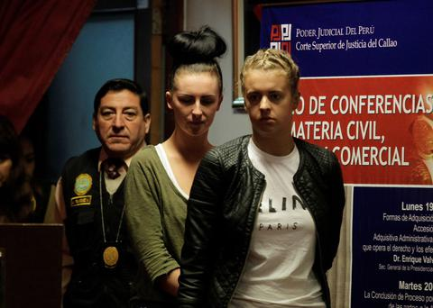 Michaella McCollum Connolly and Melissa Reid are escorted by police as they enter the Justice Court of Callao August 21, 2013. McCollum Connolly and Melissa Reid have been charged in Peru with drug trafficking and could face up to 18 years in prison if convicted, prosecutors said. McCollum Connolly, of Dungannon in Northern Ireland, and Reid, from near Glasgow in Scotland, were arrested at Lima airport two weeks ago after 11 kg (24 lb) of cocaine worth 1.5 million pounds ($2.3 million) was found in their luggage, according to authorities. REUTERS/Mariana Bazo