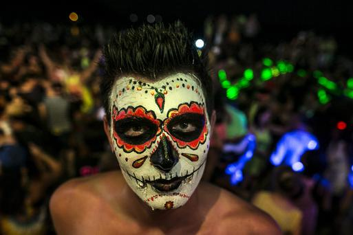 A man with a painted face looks on as hundreds of full moon partiers dance the night away on the beach of Haad Rin.