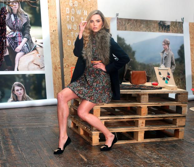 Sarah Morrissey wearing Faux Fur Collar Waffle Coat 90 euro, Tapestry Belted Skater Dress 50 euro, Tan Satchel 30 euro and loafers 40 euro, from the new A|Wear autumn winter collection.