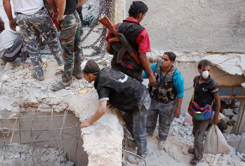 Civilians and Free Syrian Army fighters search for survivors amid the rubble of collapsed buildings after what activists said was shelling by forces loyal to Syria's President Bashar al-Assad in Aleppo's Fardous neighbourhood August 26, 2013
