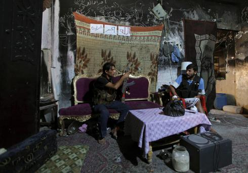 A Free Syrian Army fighter gestures as he sits on a sofa inside a room in Deir al-Zor August 26, 2013