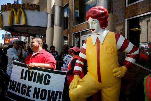 Striking McDonald's worker Bartolome Perez, 42, (L) protests outside McDonald's on Hollywood Boulevard as part of a nationwide strike by fast-food workers to call for wages of $15 an hour, in Los Angeles, California